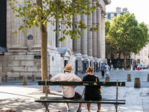 Couple on bench watches summer scene in Place Saint-Sulpice, Paris Royalty Free Stock Photo