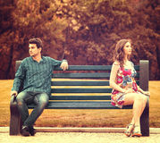 Couple on the bench. Young couple sitting apart on the bench in the park Royalty Free Stock Image