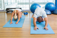 Couple in bending posture at fitness studio Stock Image