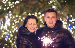Couple with Bengal light looking at camera outside over Christma Stock Photos
