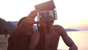 Couple of best friends taking selfie with mobile phone during beautiful sunset on tropical beach. Slow motion. HD. Couple of best friends taking selfie with stock video