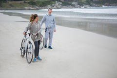 Couple with bicycle interacting with each other on beach Royalty Free Stock Image