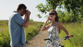 Couple with bicycle photographing by smartphone. People, technology and lifestyle concept - happy couple with bicycle photographing by smartphone at country in stock footage