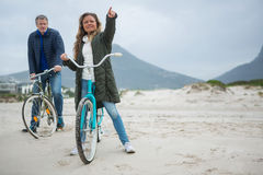 Couple on bicycle pointing at distance on beach. During winter Stock Images