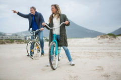 Couple on bicycle pointing at distance on beach Royalty Free Stock Images