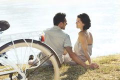 Couple with bicycle resting in front of the lake royalty free stock photos