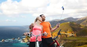Couple with bicycle and smartphone selfie stick Royalty Free Stock Photography