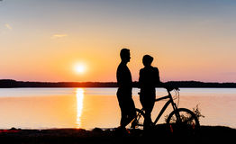 Couple on a bicycle at sunset by the lake Stock Photography