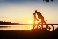 Couple on a bicycle at sunset by the lake Royalty Free Stock Photography