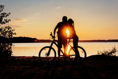Couple on a bicycle at sunset by the lake Stock Photos