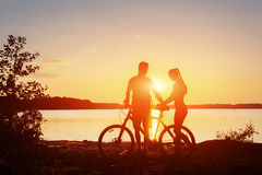 Couple on a bicycle at sunset by the lake Royalty Free Stock Photo