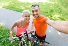 Couple with bicycle taking selfie outdoors Stock Images