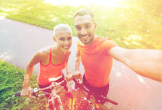 Couple with bicycle taking selfie outdoors Stock Photography