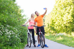 Couple with bicycle taking selfie by smartphone Stock Photos