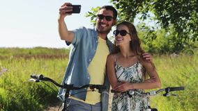 Couple with bicycle taking selfie by smartphone. People, technology and lifestyle concept - happy couple with bicycles taking selfie by smartphone at country in stock footage