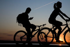 Couple bicycler on sunset. Couple bicycler  ride on sunset and call by phone Royalty Free Stock Image