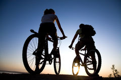 Couple on bicycles. Couple of bicyclists on the brink of a rock looks at a sunset Stock Image