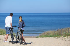 Couple with bicycles by the beach Stock Image