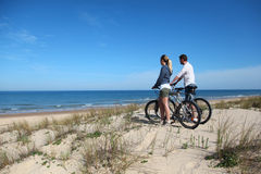 Couple with bicycles on the beach Royalty Free Stock Image