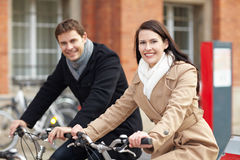 Couple on bicycles in city Royalty Free Stock Photos