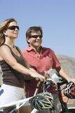Couple With Bicycles Looking Away Royalty Free Stock Photography