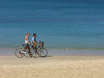 Man and woman with bicycles on sea beach Stock Image