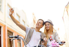 Couple with bicycles taking photo with camera Stock Images