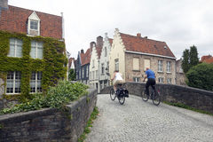 Couple on bicycles try to ride over old medieval bridge in cente Stock Photos