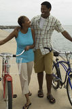 Couple With Bicycles Walking On Beach stock image