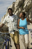 Couple With Bicycles Walking On Beach Stock Images