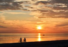 Couple of bicyclists walking along the seashore Royalty Free Stock Photo