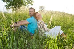 Couple in big green grass back to back. Man and woman sitting in the field in summer day. royalty free stock photography