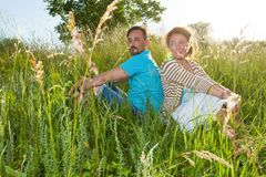 Couple in big green grass back to back. Man and woman sitting in the field in summer day. loving couple gently peacefully gossipin royalty free stock images