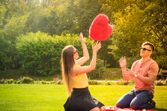 Couple with big heart on picnic Royalty Free Stock Images