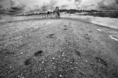 Couple with bike in the beach in black and white stock images