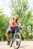 Couple on a bike outdoor smiling Royalty Free Stock Image