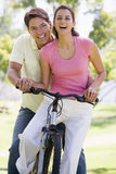 Couple on a bike outdoors smiling.  Stock Photo