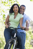 Couple on a bike outdoors smiling stock photography