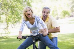 Couple on bike outdoors smiling and acting scared Royalty Free Stock Photos
