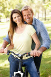 Couple with bike in park Royalty Free Stock Image