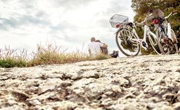 Couple on a bike trip. Lovers sitting on beach. Couple on a bike trip. Lovers sitting on beach, rock, cliff by the sea or forest in nature. Bicycles parked for royalty free stock photos