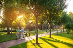Couple with bike is walking. Senior people outdoors. Admire the beauty around you. One more summer spent together Royalty Free Stock Photos
