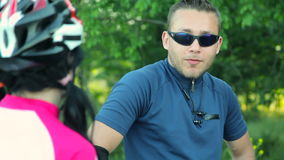 Couple of bikers talking. Close up of couple of bikers talking to each other. Young man in sunglasses and girl in cyclist helmet stock footage