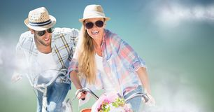 Couple on bikes against blue green background with clouds Stock Photography