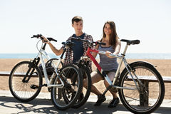 Couple with bikes on beach Stock Images