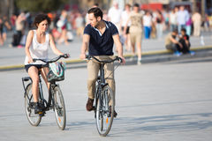 Couple with bikes on a city beach Stock Images