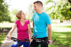 Couple on bikes outdoors Stock Image