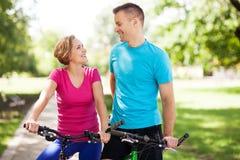 Couple on bikes outdoors Stock Image