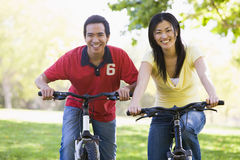 Couple on bikes outdoors smiling Royalty Free Stock Photography