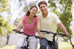 Couple on bikes outdoors smiling Royalty Free Stock Photo
